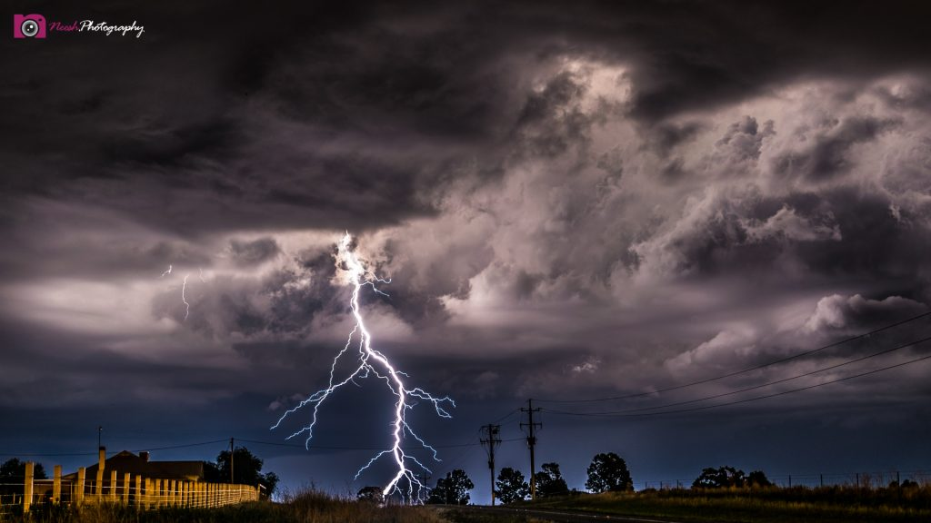 Astrophotography and Storm Chasing – Large lightening bolt near road