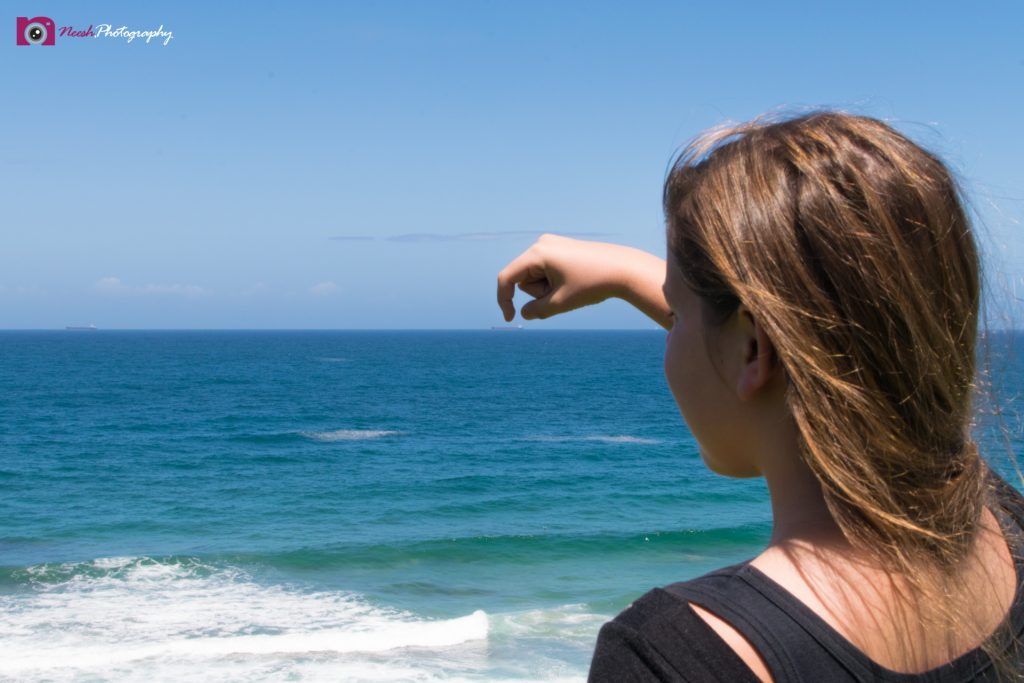 Road Trips - Girl with finger above ship on horizon